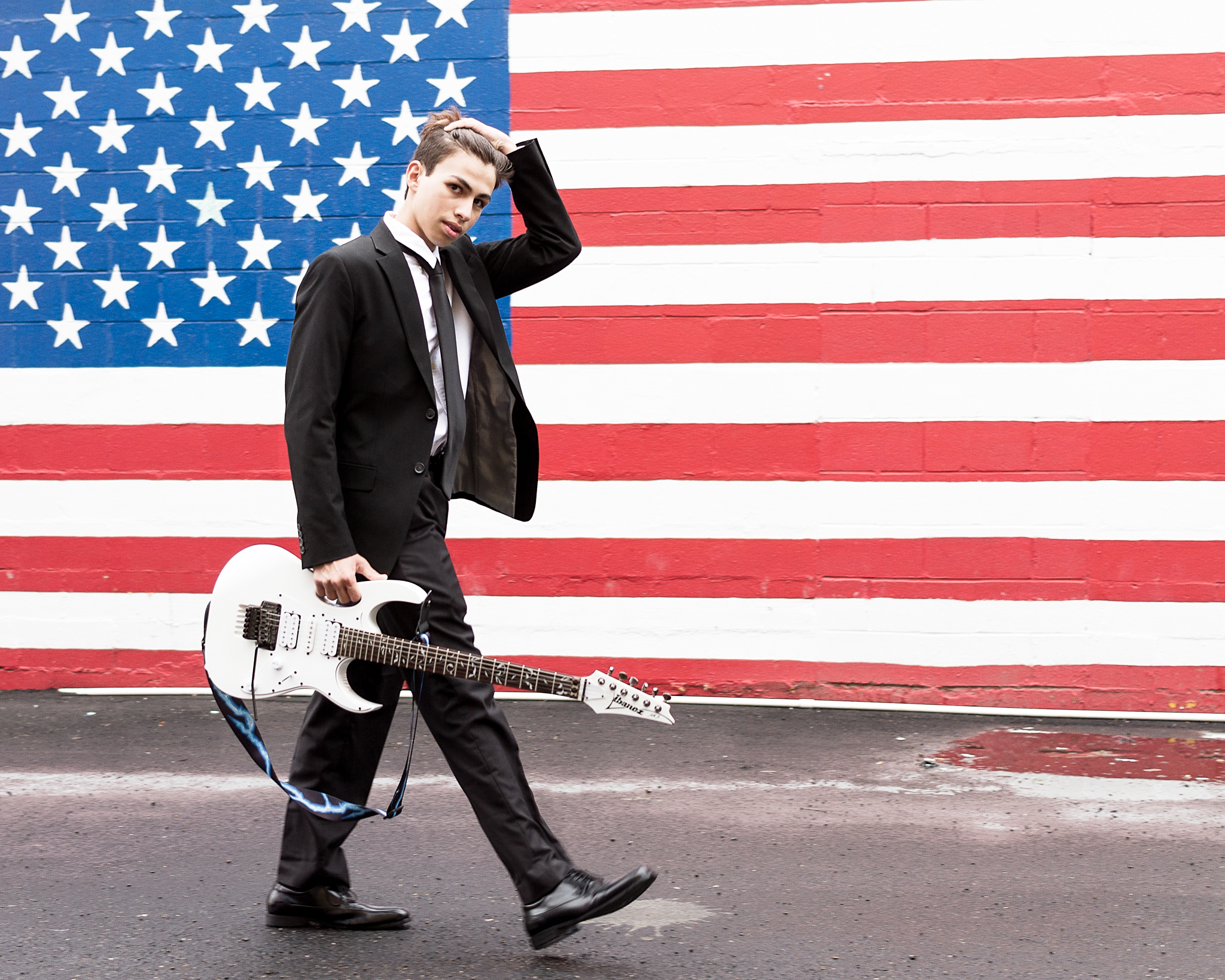 Walking with guitar in front of American Flag